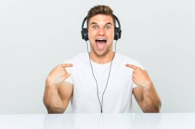 Young man listening to music with headphones surprised pointing at himself, smiling broadly.