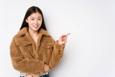 Young chinese woman posing in a white background isolated smiling cheerfully pointing with forefinger away.