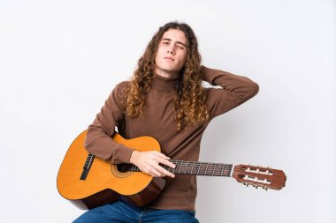 Young caucasian man playing guitar isolated touching back of head, thinking and making a choice.