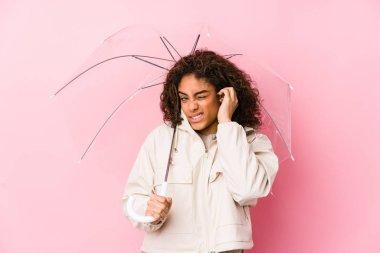 Young african american woman holding a umbrella covering ears with hands.