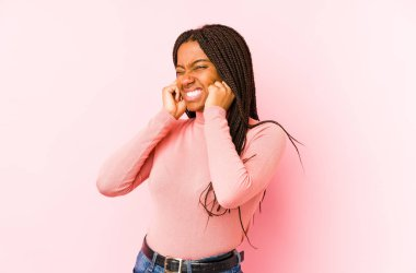 Young african american woman isolated on a pink background covering ears with hands.