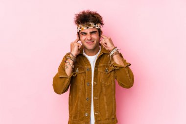 Young hipster man isolated Young man going to a festival covering ears with hands.