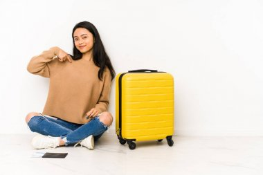 Young chinese traveler woman sittting on the floor with a suitcase isolated person pointing by hand to a shirt copy space, proud and confident