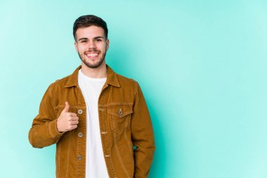 Young handsome man smiling and raising thumb up