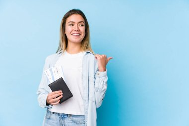 Young caucasian woman holding a passport isolated points with thumb finger away, laughing and carefree.