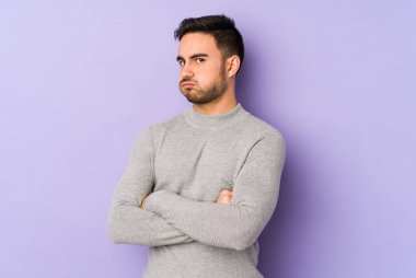Young caucasian man isolated on purple background tired of a repetitive task.