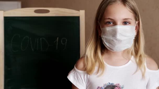Egy kislány otthon álarcban áll, és a kezével mutatja az osztályt a Covid-19 felirat mögött.