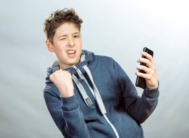 Emotions and joy of a young man when using a mobile phone. Photo of a young man in a gray sports jacket on a background of prevailing light shades