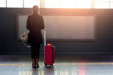 Woman with red suitcase standing in airport on front of flight t