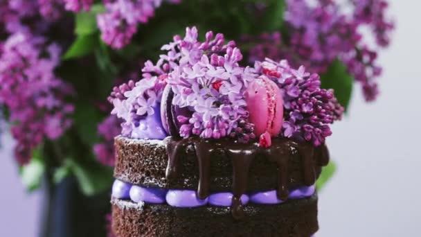 Točící se vršek vícevrstvého svatebního dortu zdobeného čokoládovou polevou, šlehačkou, šeříkovými květy, růžovými a fialovými makaróny. Jarní dezert.
