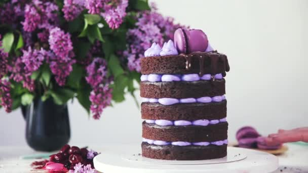 Making multi-layered wedding cake in spring style. Dessert is decorated with macaroons, lilac flowers, liquid chocolate coating. Brown and violet confectionery product. Bouquet of lilacs in a vase.