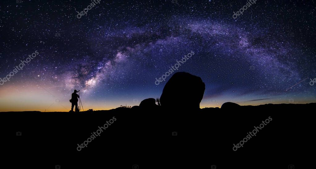 Astro Photographer in a Desert Landscape with view of Milky Way Galaxy