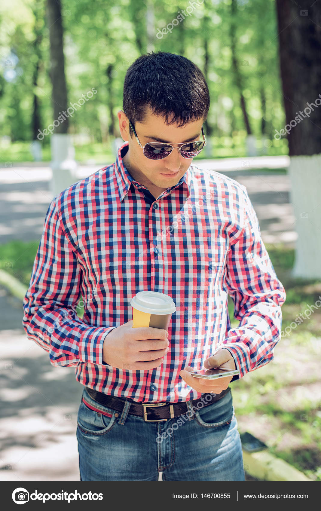 0285b99e0c A man in a shirt and jeans and sunglasses