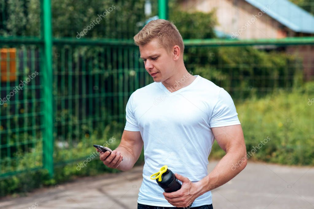 A male athlete goes in for sports in the open air. Muscular arms. Blonde in a white T-shirt. Lifestyle of the bodybuilder