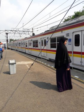 Stasiun duri, Jakarta, Indonesia - July 03, 2016 : A Muslim woman is waiting, to take an electric train