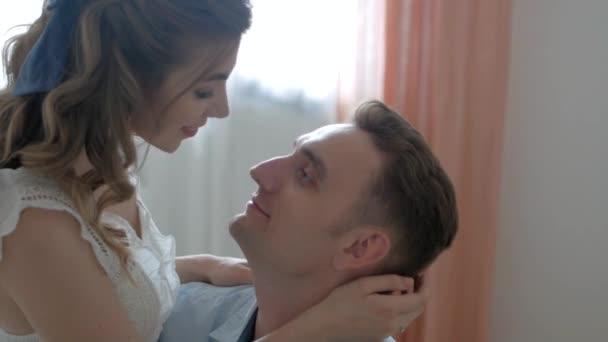 muž a dívka v bytě na posteli, naproti polibku z okna