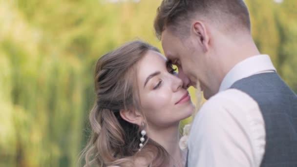 Der Bräutigam küsst die Braut, die auf einer Holzbrücke an einem grünen See steht, mit geschlossenen Augen vor dem Hintergrund von Bäumen in Großaufnahme, das Brautpaar wird hoch