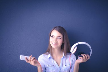 Smiling girl with headphones sitting on the floor near wall