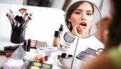 Mladá krásná žena, takže make-up zrcadla, sedící u stolu