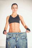 Fotografie Fitness mladá žena ukazuje, že své staré džíny