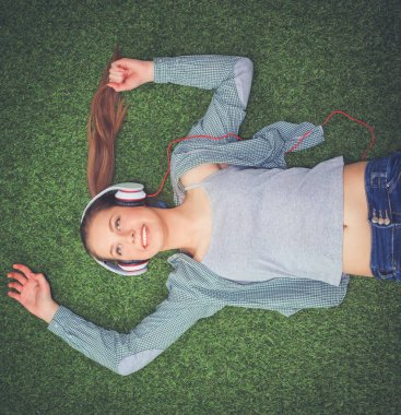 Relaxed woman listening to the music with headphones lying on  grass