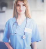 Fotografia Ritratto di medico donna con cartella al corridoio di ospedale