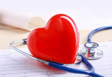 Red heart and a medical stethoscope at desk