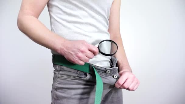 The guy looks in his pants with a magnifying. Small penis.