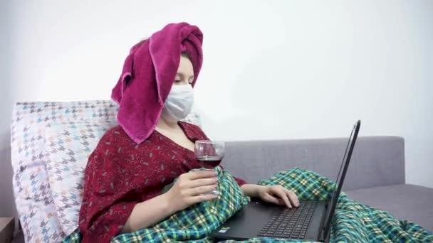 Mädchen trinkt Wein und arbeitet zu Hause in Quarantäne.