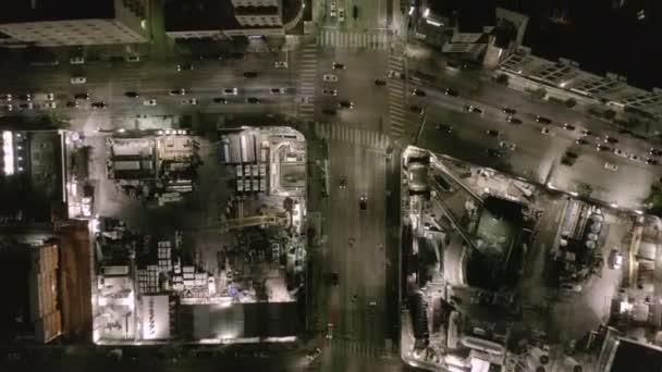 AERIAL: Blick über die Kreuzungsstraße mit Großbaustelle und Erdlöchern in der Nacht mit leuchtenden Straßen und City-Ampeln