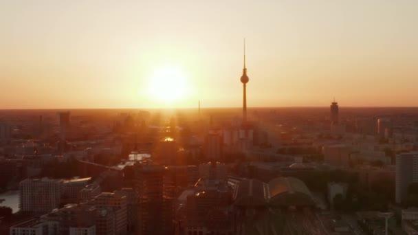 AERIAL: Let nad Berlínem, Německo při krásném západu slunce, Sluneční světlo a pohled na Alexanderplatz TV Tower a Ostbahnhof, Sunflairs