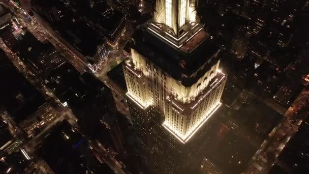 AERIAL: Dech beroucí kruh nad ikonickou Empire State Building nahoře osvětlil paralelní ulice a křižovatky obytných bytů a kancelářských budov v Midtown Manhattan, New York City v noci