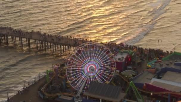 AERIAL: Přichází dolů na Santa Monica Pier Ferrys Wheel, Los Angeles při krásném západu slunce s turisty, chodci procházky baví na téma park horská dráha s výhledem na oceán vlny shazovat