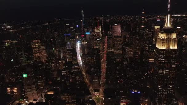 AERIAL: Breathtaking wide view the iconic Empire State Building above lit up parallel avenues and junctions residential condominiums and office buildings in Midtown Manhattan, New York City at night