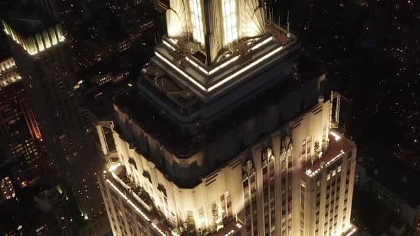 Epický záběr z blízka helikoptéry říšského státu, vypouklé nad osvětlenými paralelními uličkami a křižovatkami obytných domů a kancelářských budov v Midtown Manhattan, New York City v noci
