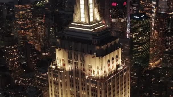 AERIAL: Repülő felett világított párhuzamos utak és csomópontok, lakóházak és irodaházak Midtown Manhattan, New York City éjjel. Közúti infrastruktúra nagyvárosban