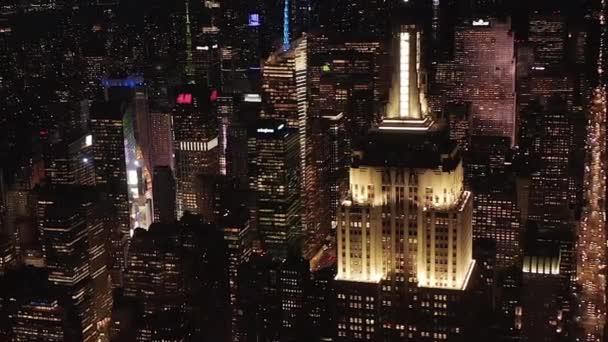 AERIAL: lélegzetelállító széles kilátás nyílik az ikonikus Empire State Building felett világított párhuzamos utak és csomópontok lakóházak és irodaházak Midtown Manhattan, New York City éjjel