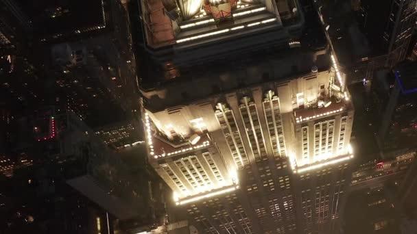 AERIAL: Dech beroucí let nad ikonickou Empire State Building nahoře osvětlil paralelní cesty a křižovatky obytných bytů a kancelářských budov v Midtown Manhattan, New York City v noci