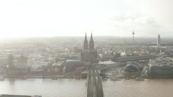 AERIAL: Kölner Hohenzollernbrücke und Blick auf den Dom im nebligen Sonnenlicht
