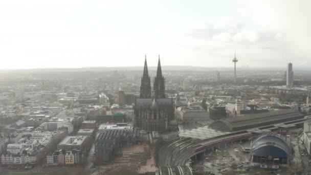 AERIAL: Kölner Hohenzollernbrücke und Blick auf den Dom mit Hauptbahnhof im nebligen Sonnenlicht