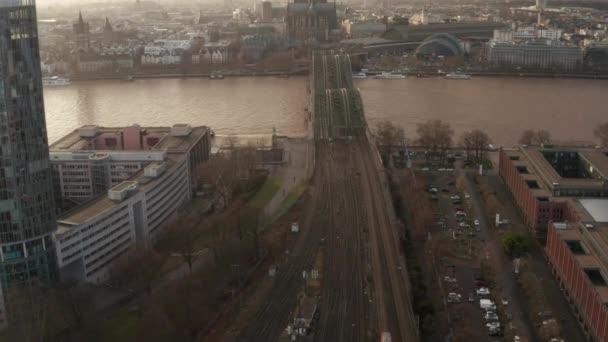 AERIAL: Blick über die Kölner Hohenzollernbrücke und den Dom im nebeligen Sonnenlicht