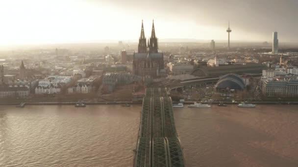 AERIAL: Blick über die Kölner Hohenzollernbrücke und Blick auf Dom und Fernsehturm im nebligen Sonnenlicht