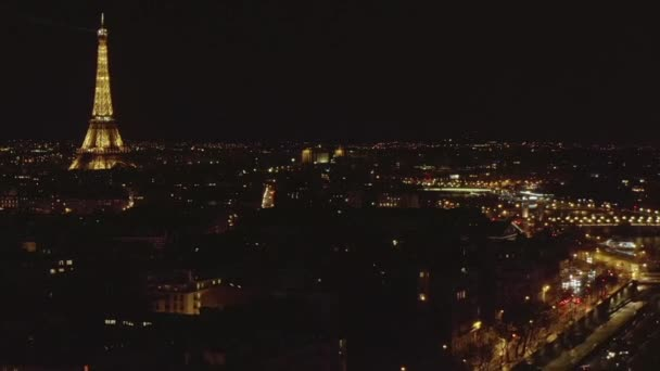 AERIAL: Reverse Drone Flight from Eiffel Tower, Tour Eiffel in Paris, France at Night with City Lights