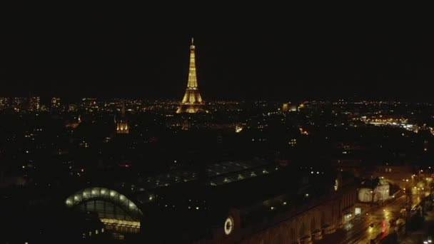 AERIAL: View over Seine River at Night in Paris, France with View on Eiffel Tower, Tour Eiffel Shining light and Beautiful City Lights