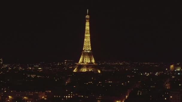 AERIAL: Pomalu krouží Eiffelova věž, Tour Eiffel v noci po Paříži, Francie s krásnými městskými světly