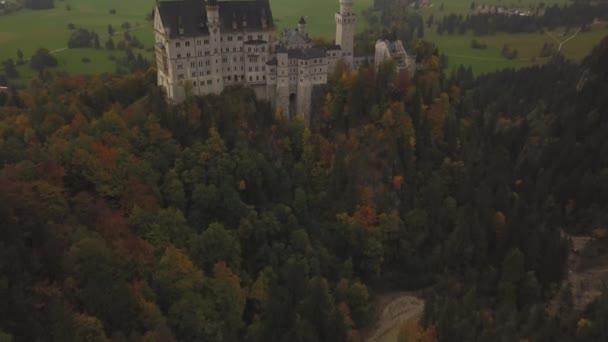 AERIAL: Blick auf Schloss Neuschwanstein im Wald, Berge, Sommer, Nebel, bunt