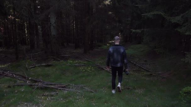 SLOW MOTION: Mladý muž, fotograf kráčející do lesa s kamerou a fotit léto