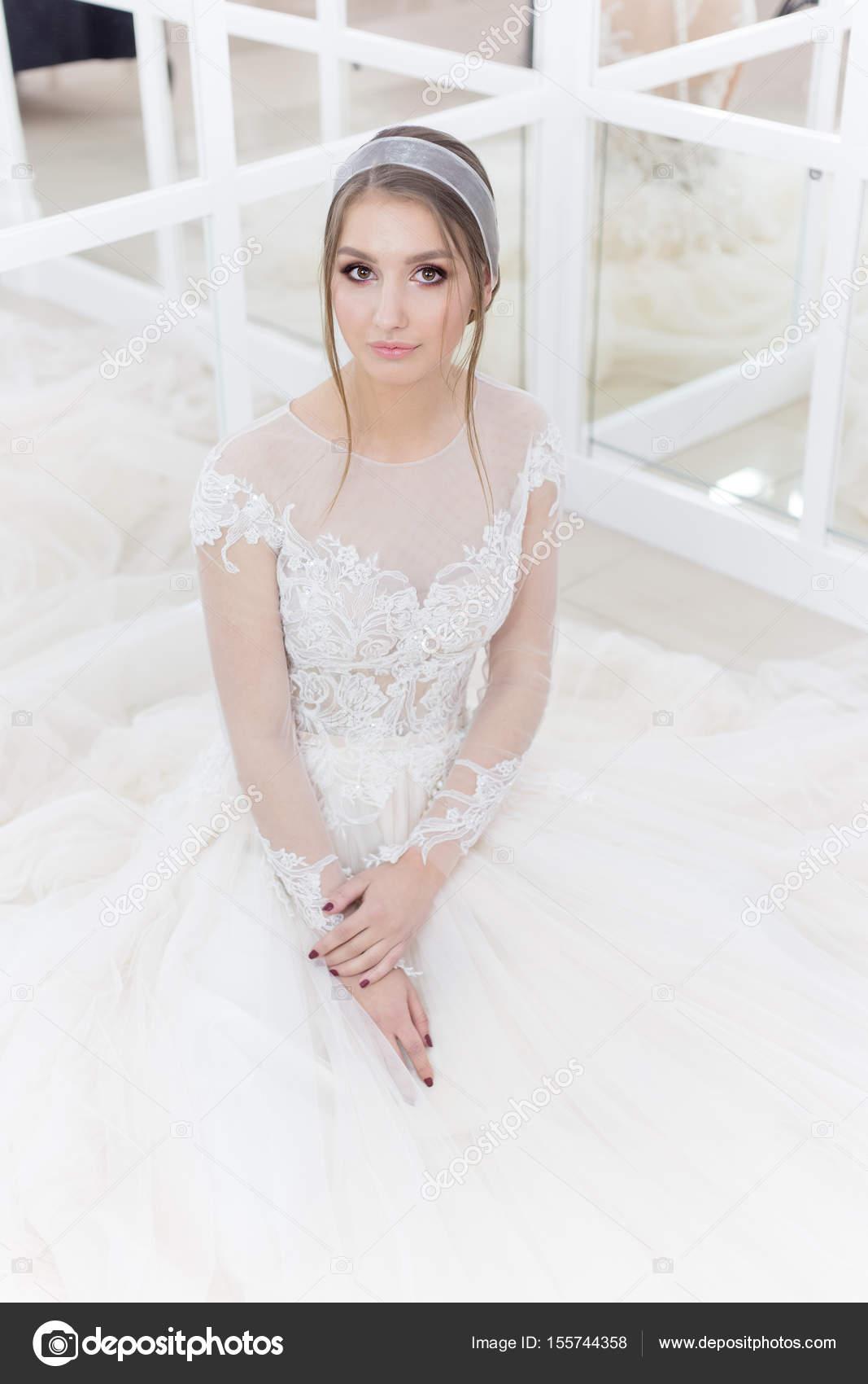 Beautiful cute tender young girl bride in wedding dress in mirrors ...