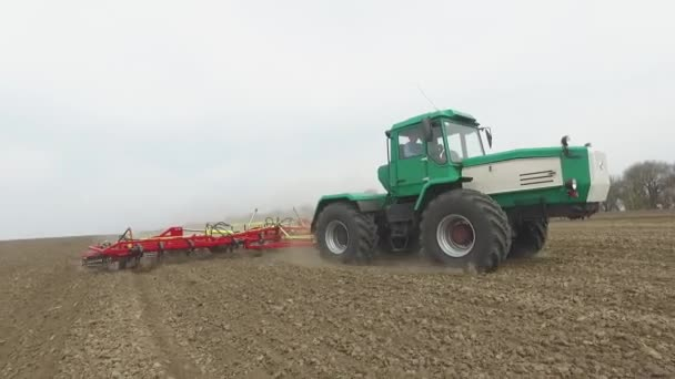 Green tractor and red cultivator plows the ground on the field in the spring