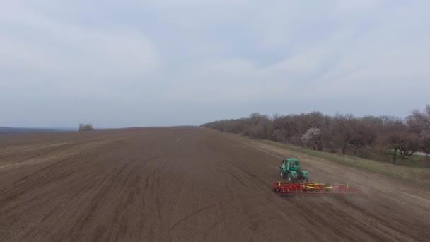 Luftaufnahme. Traktor und Grubber arbeiten auf dem Feld